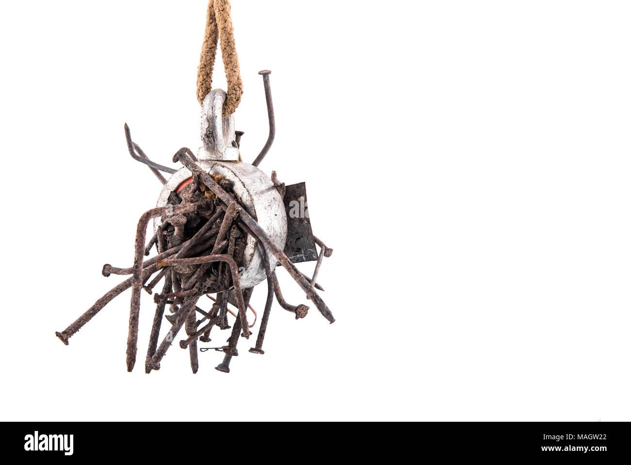 Deux voies de recherche en acier aimant avec clous rouillés suspendu à la corde, isolé sur fond blanc Photo Stock