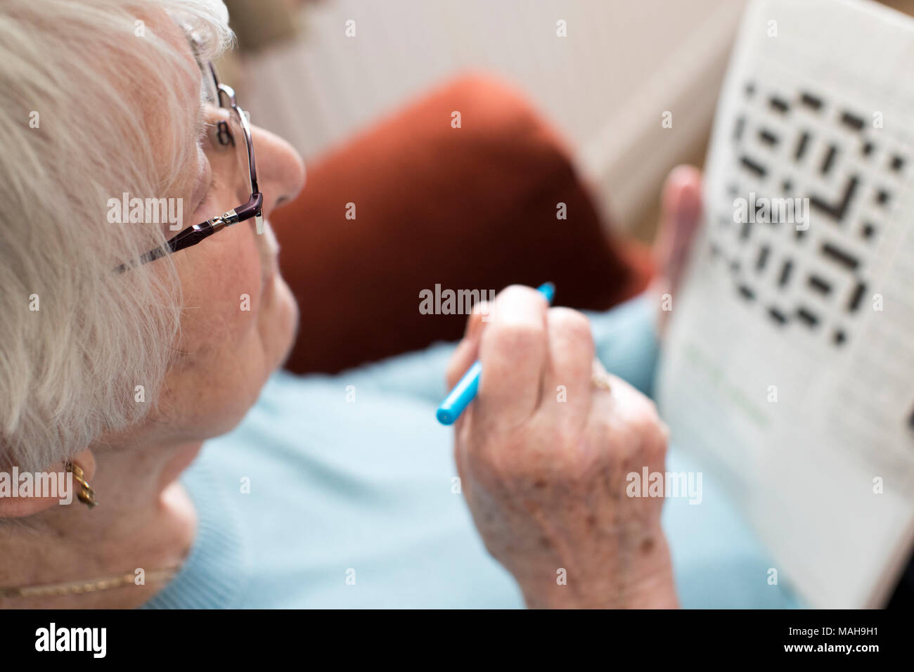 Senior woman doing Crossword Puzzle à la maison Photo Stock
