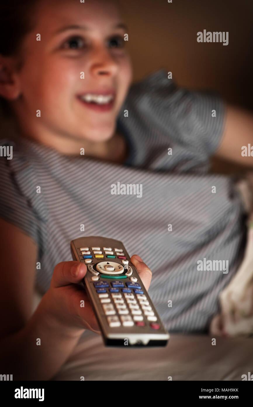 Jeune fille au lit regarder la télévision pendant la nuit Photo Stock