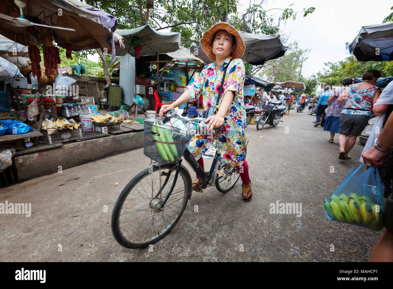 Femme d'âge moyen à vélo autour du marché Chhlong, Kratie Province, le Cambodge en Asie du sud-est Banque D'Images