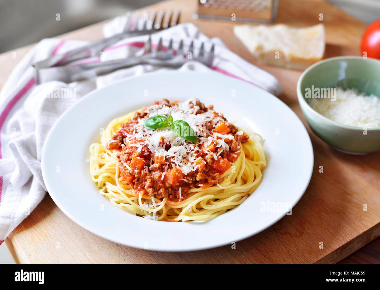 Repas délicieux plats de pâtes, spaghettis à la bolognaise sur une plaque blanche. Plat de pâtes, cuisine italienne traditionnelle avec le parmesan, les viandes hachées et feuille de basilic. Photo Stock