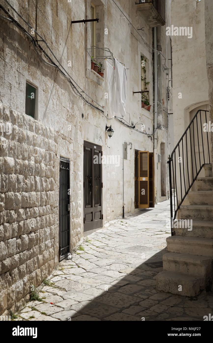 Jour de lessive en Italie avec couvertures blanches accroché à sécher d'une maison en pierre dans une ruelle pavée dans une ancienne ville italienne. Photo Stock
