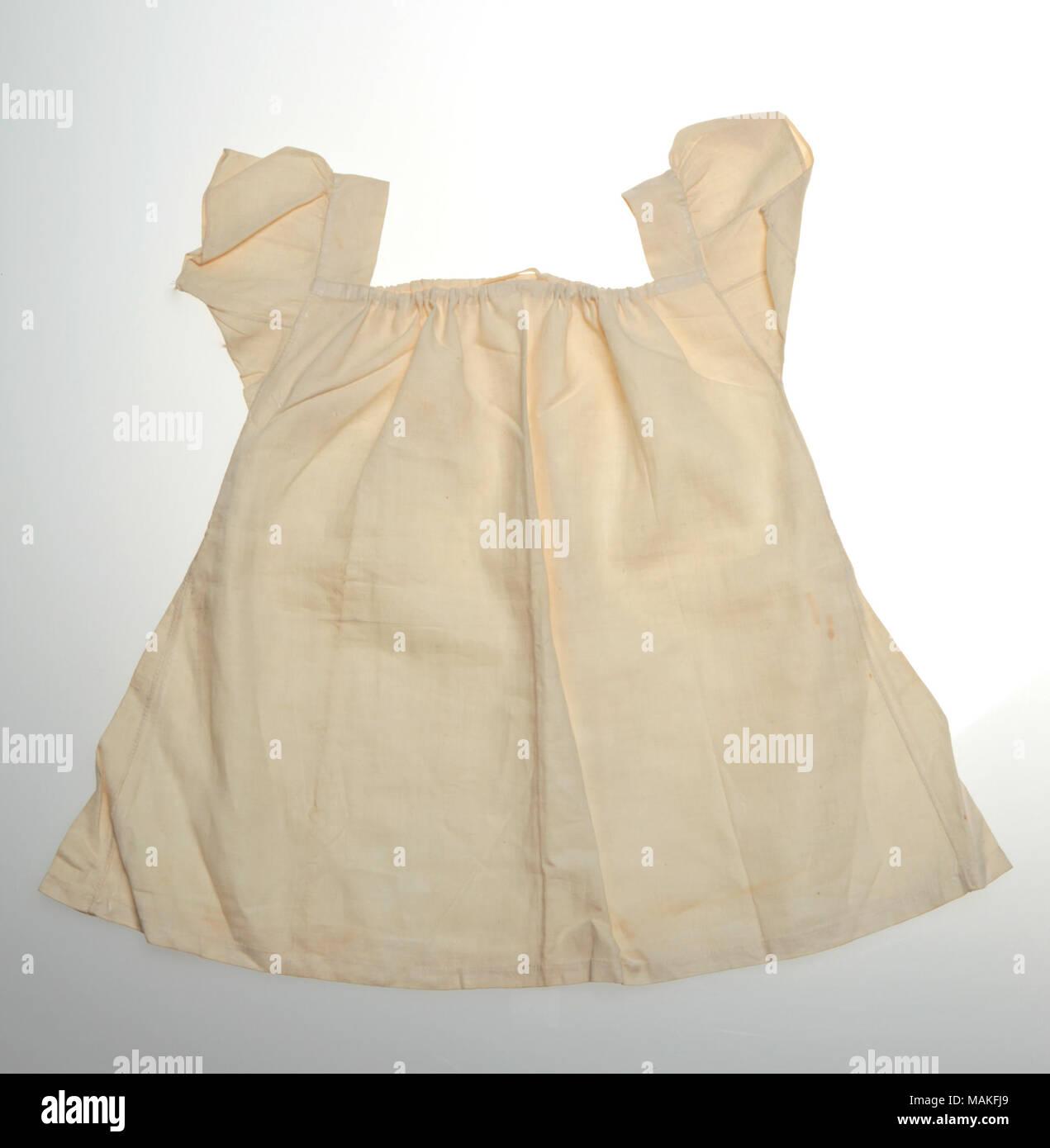 Off-white , plainweave chemise du nourrisson avec cordon de cou, manches courtes, et des goussets sous les bras. Titre: Infant's Off-White Chemise . après 1820. Photo Stock