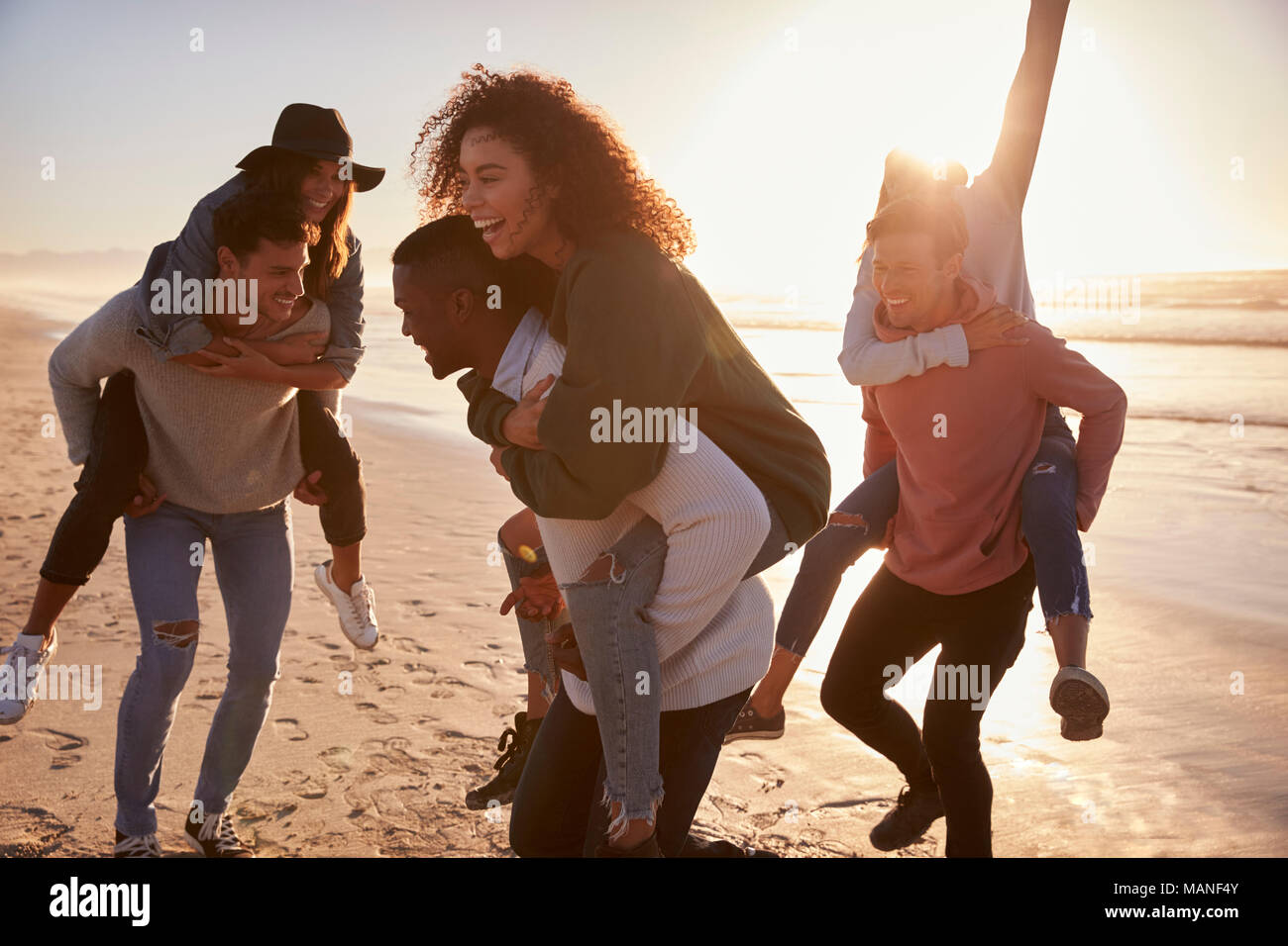Groupe d'amis ayant la race de ferroutage sur l'ensemble de la plage d'hiver Photo Stock