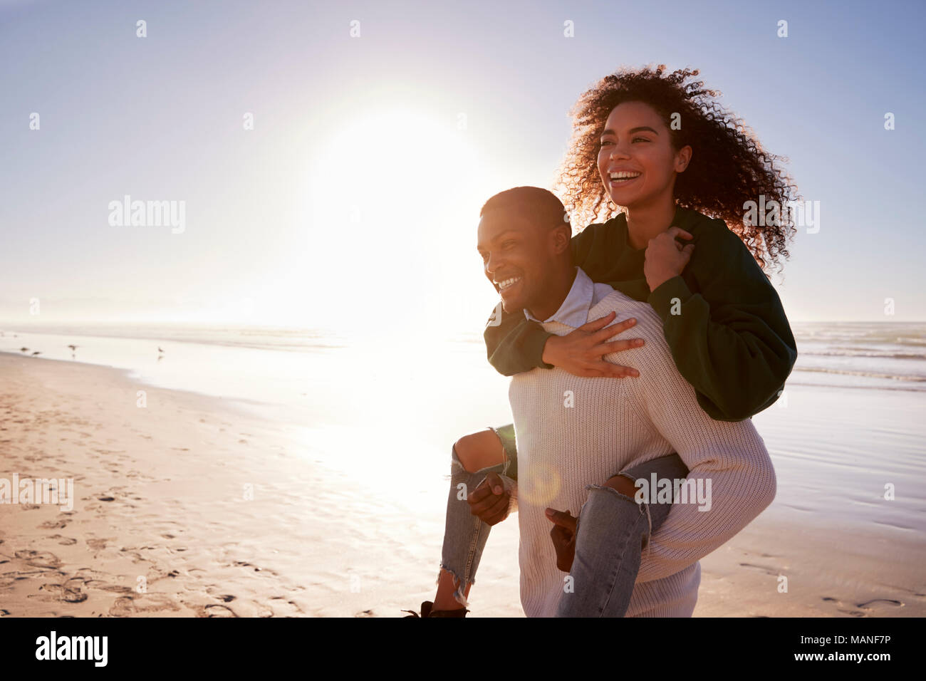 Man Giving Woman Piggyback sur Winter Beach Locations Photo Stock