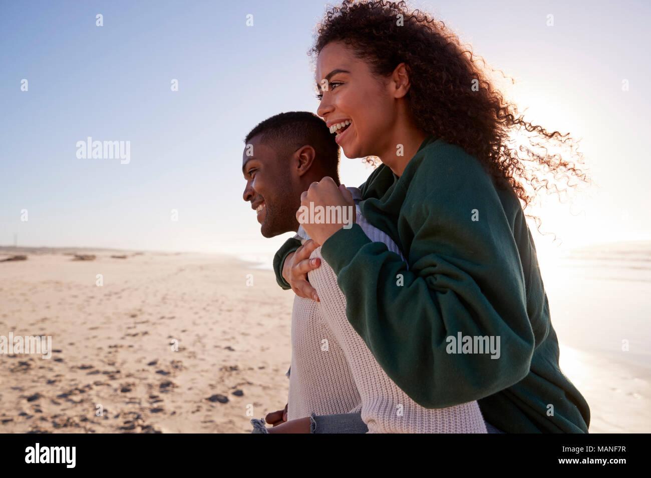 Man Giving Woman Piggyback sur Winter Beach Locations Photo Stock