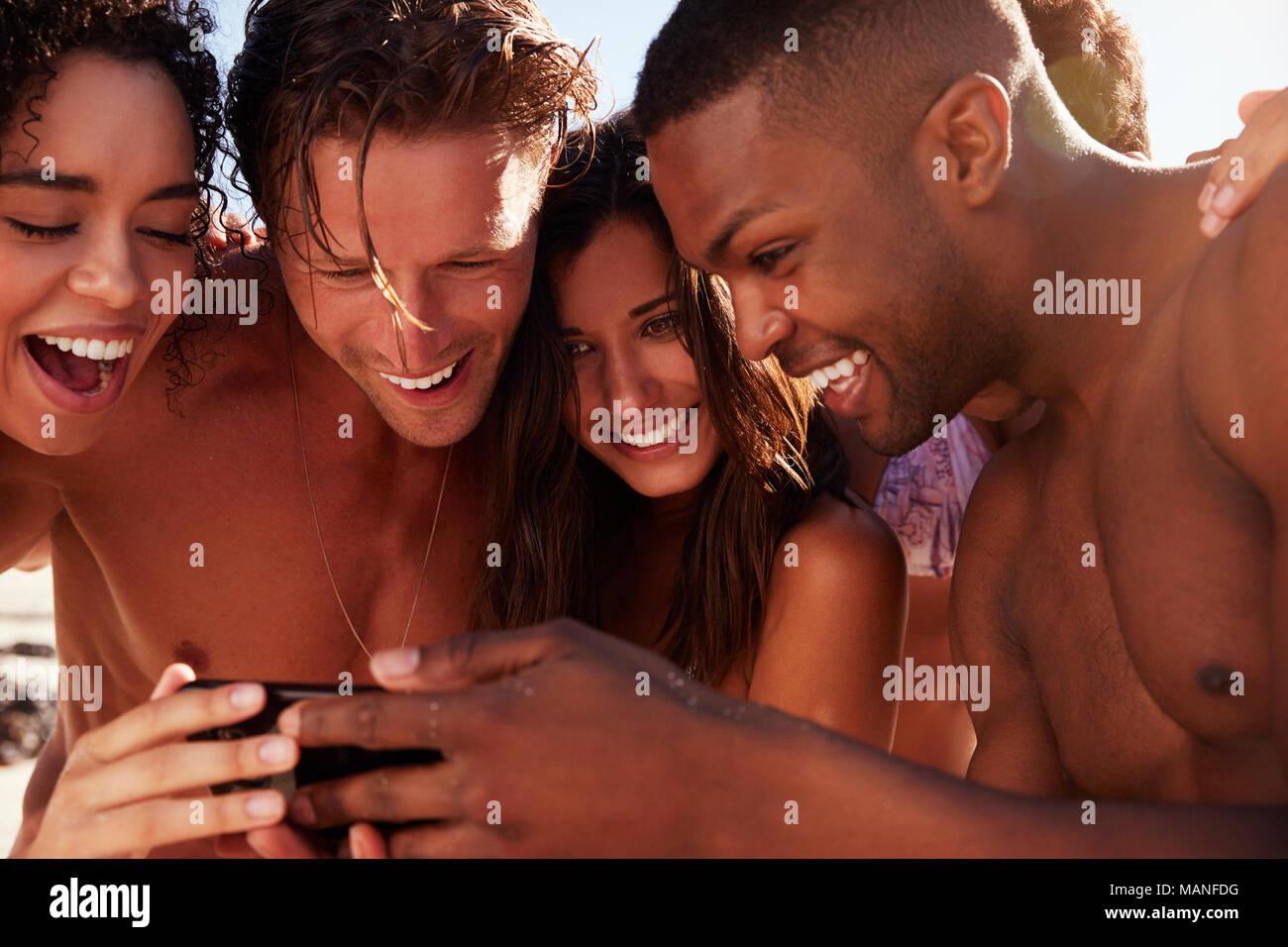 Amis de vacances de plage à la recherche de photo sur téléphone mobile Banque D'Images