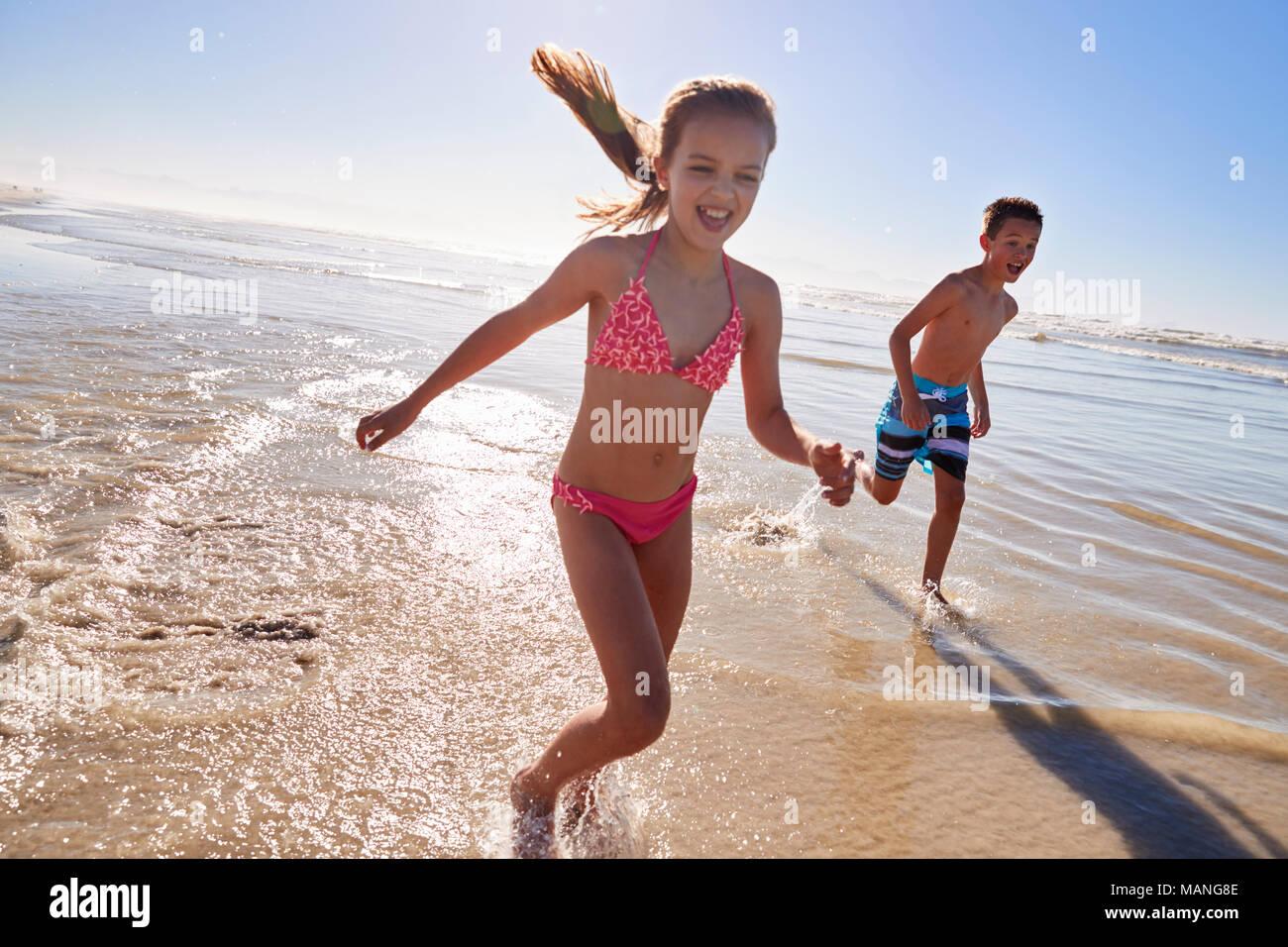Garçon et fille en vacances en marche à travers les vagues Photo Stock