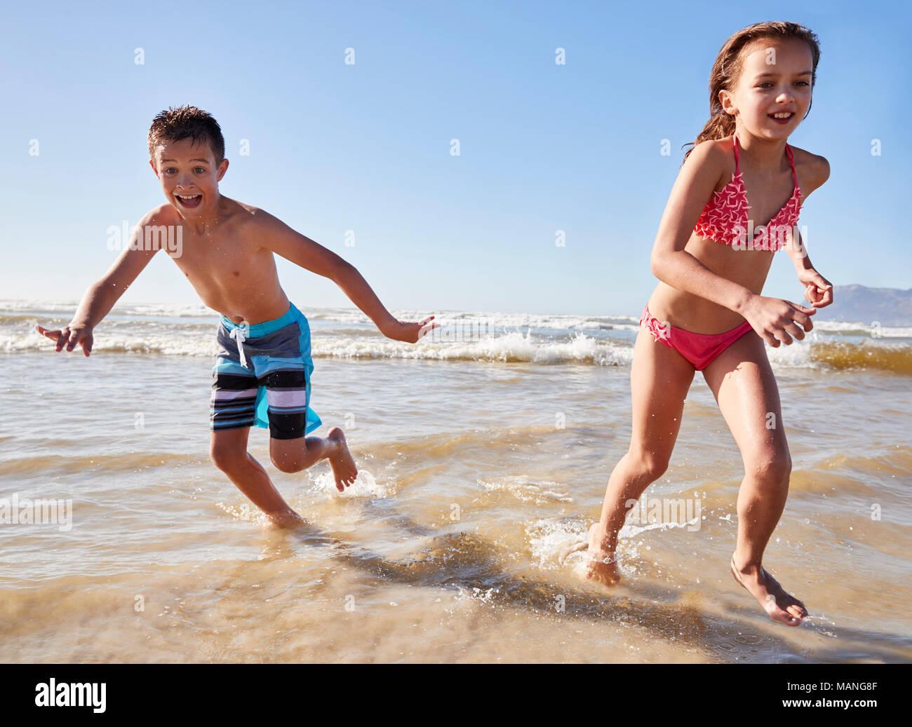 Garçon et fille en vacances en marche à travers les vagues Banque D'Images