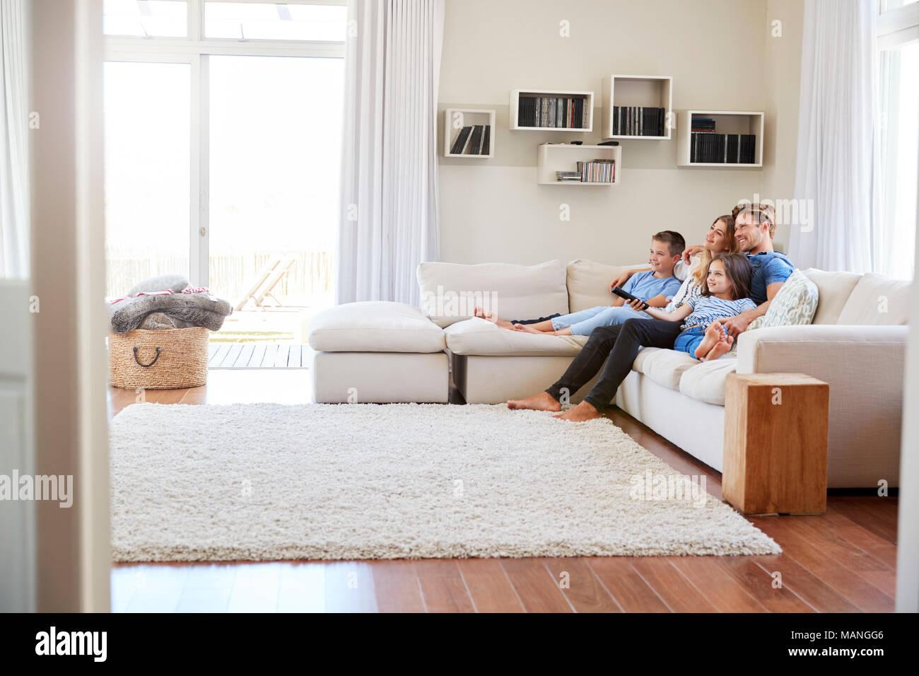 Family Sitting on Sofa à la maison à regarder la télévision ensemble Photo Stock