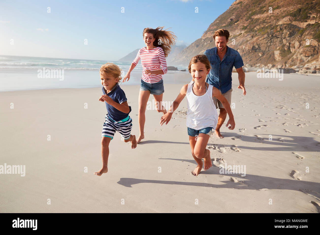 Les parents le long de plage avec les enfants en vacances Photo Stock