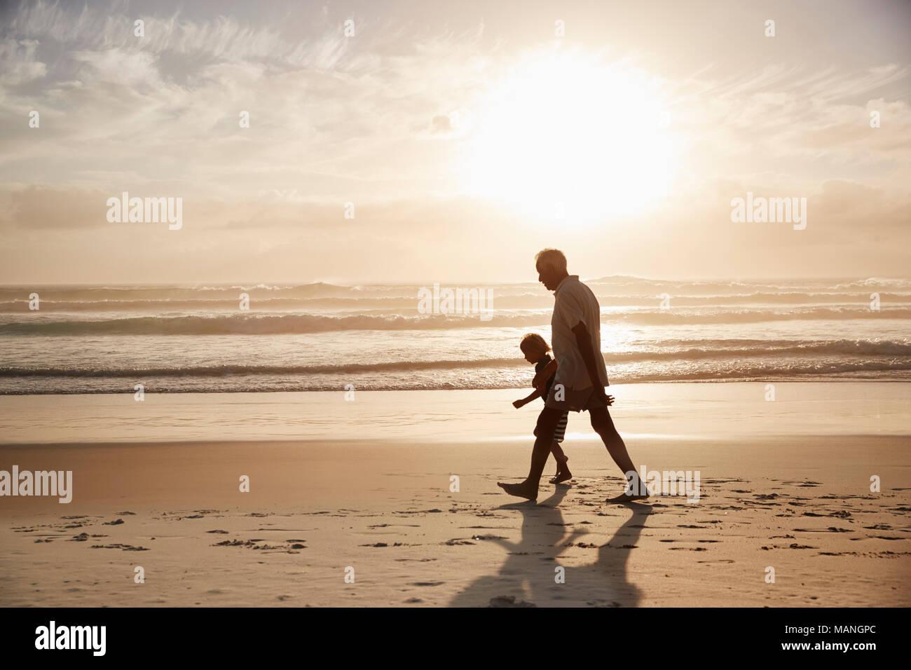 Silhouette de grand-père marcher le long de plage avec petit-fils Photo Stock