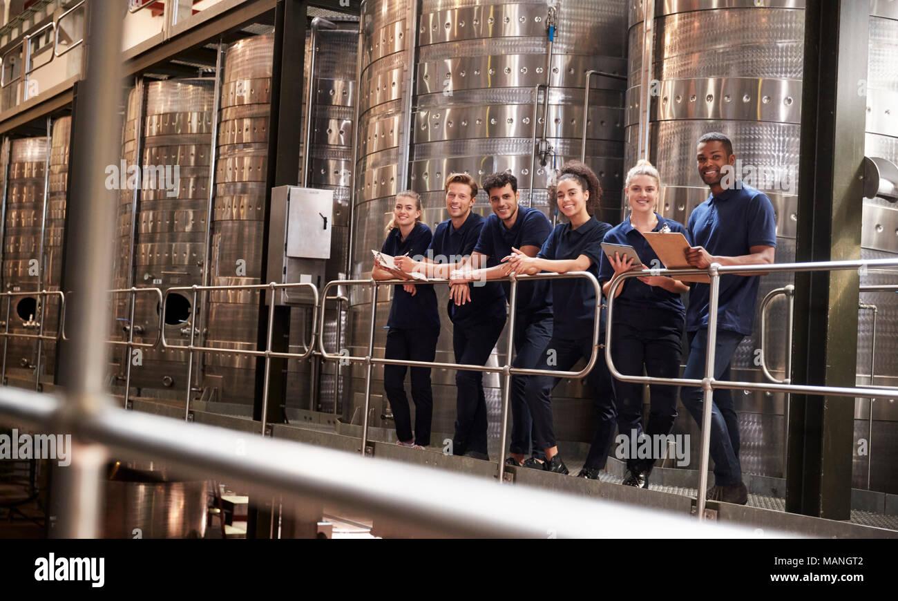 Le personnel d'une usine de vin en souriant à l'appareil photo à partir d'une passerelle Photo Stock