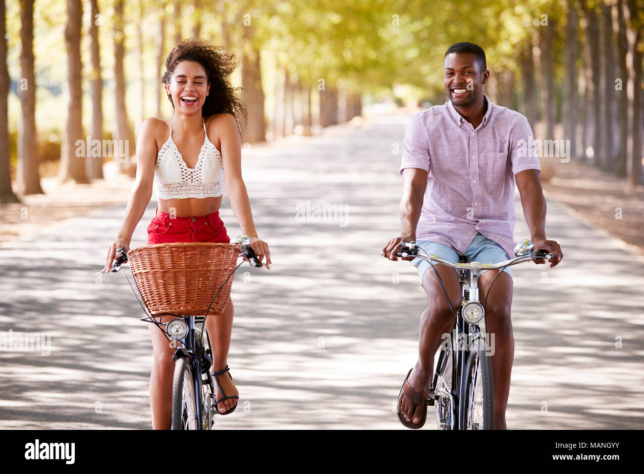 Young caucasian couple riding bicycles sur une route bordée d'arbres Banque D'Images