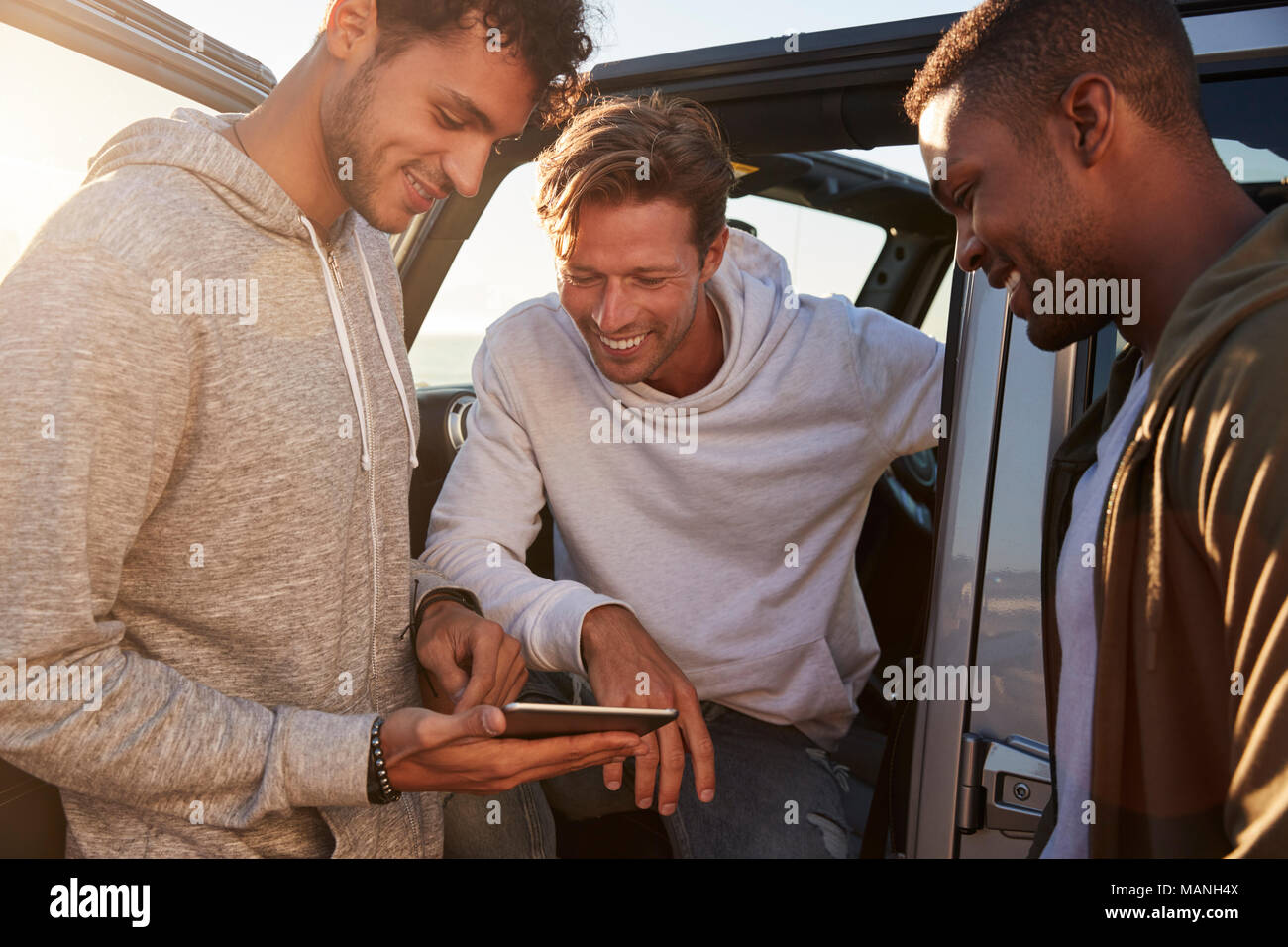 La planification d'amis masculins route road trip with tablet computer Photo Stock