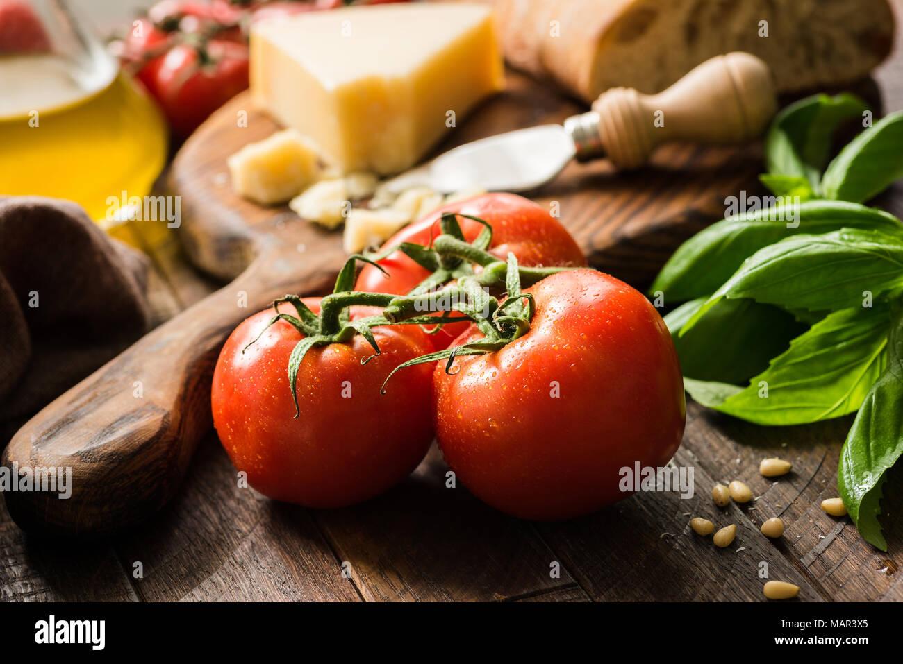 Tomates sur vigne, l'huile d'olive et parmesan. Arrière-plan de l'alimentation italienne ou still life Photo Stock