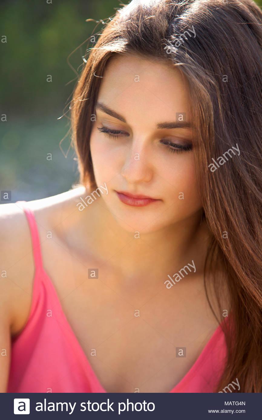Jeune femme brune, 20 ans à la recherche de l'appareil photo. de rêve avec les yeux baissés. Tiré de la tête et des épaules. Photo Stock