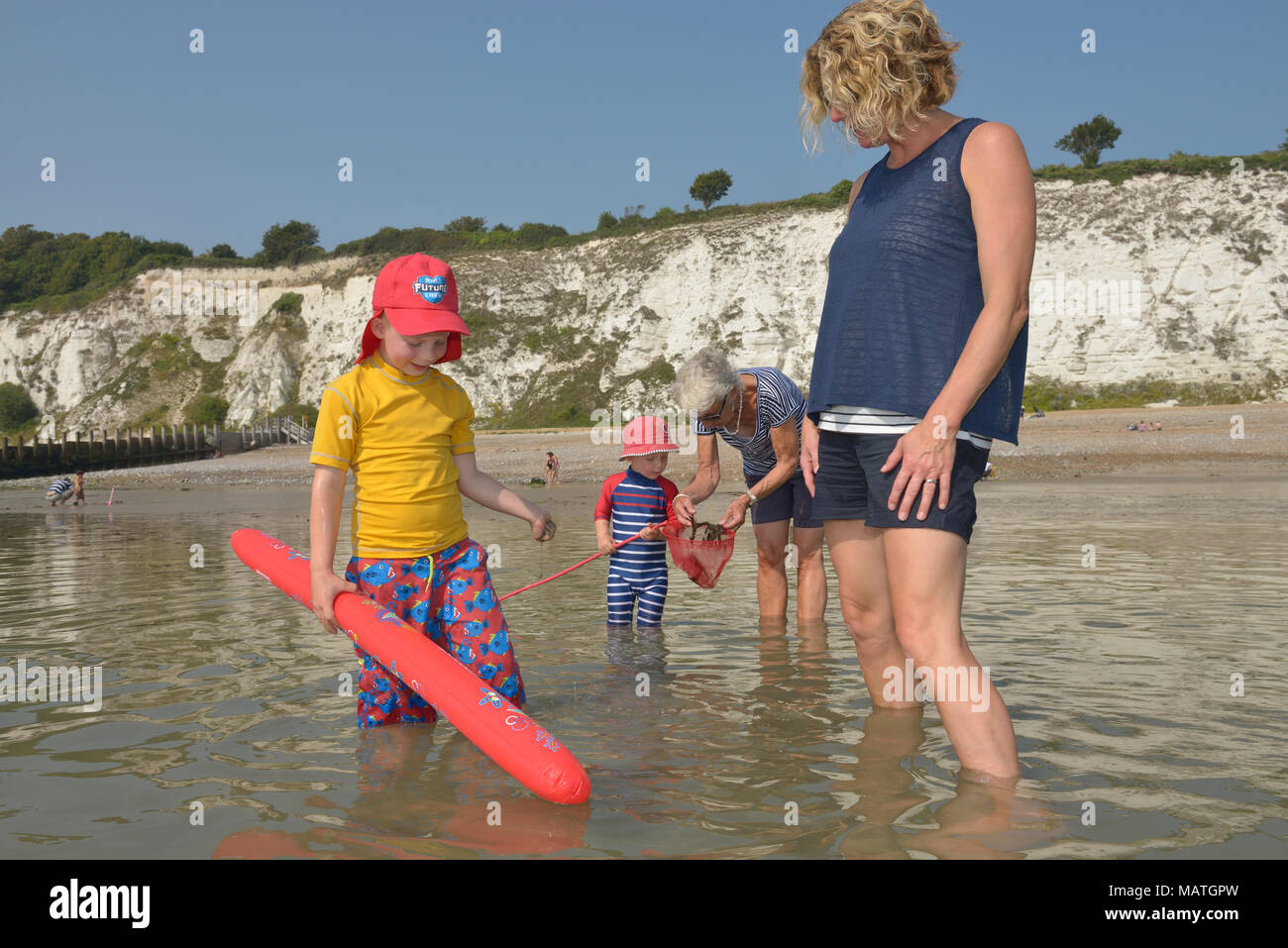 Multi generation family running in the sea, Eastbourne, East Sussex, England, UK Photo Stock