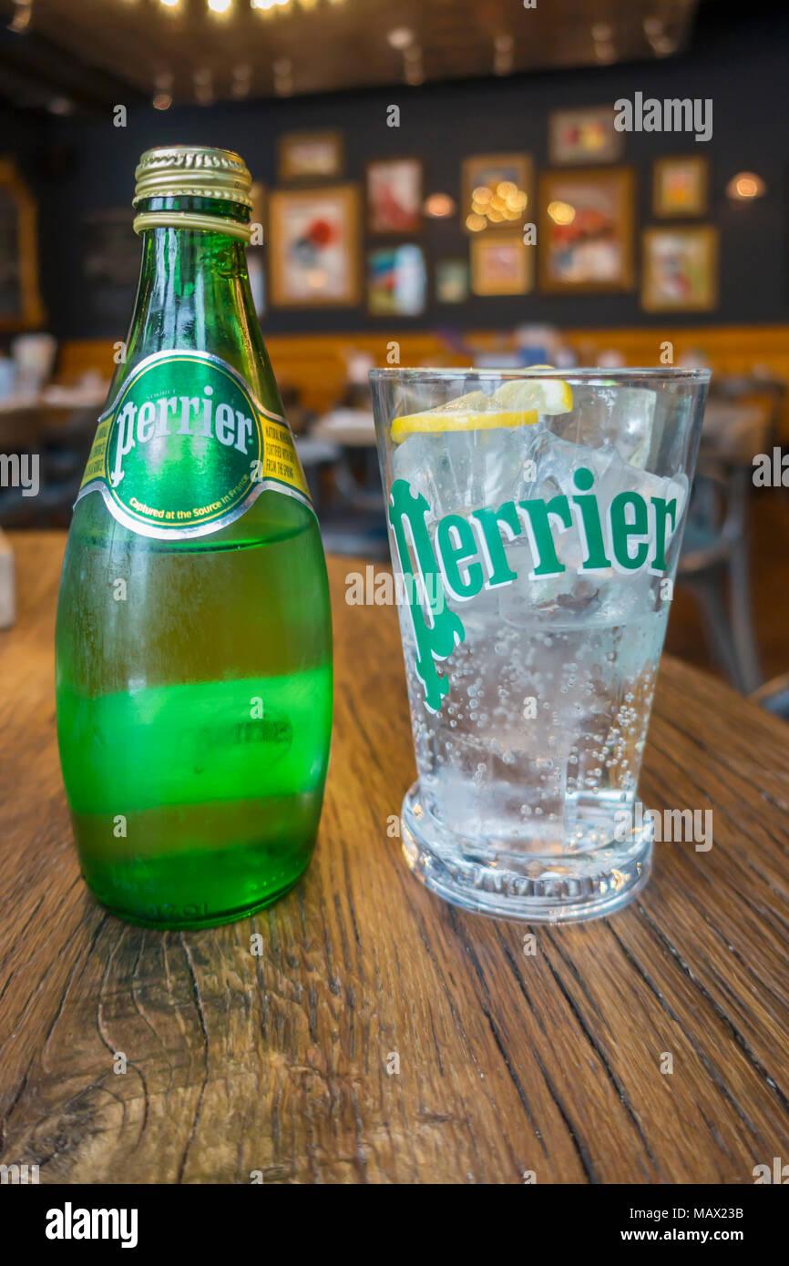 7a082377cc Un verre et une bouteille d'eau minérale Perrier pétillant froid dans un  café de style français