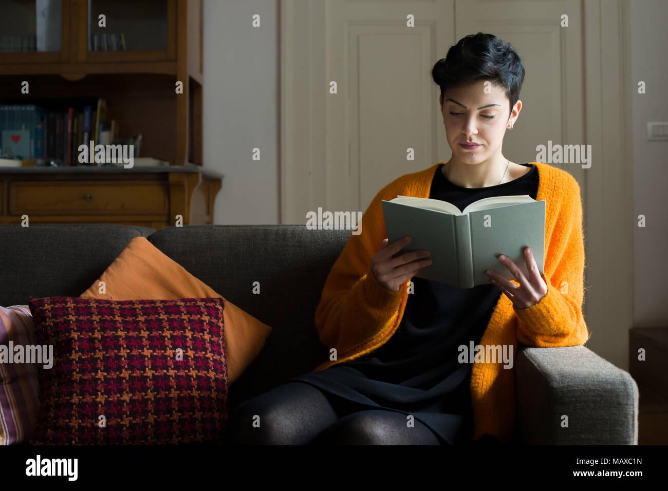 Femme aux cheveux courts la lecture d'un livre sur un canapé Photo Stock