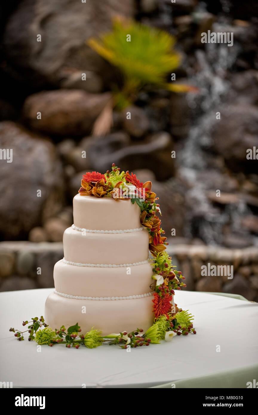 Un gâteau de mariage crémeux en couches par l'emballage des fleurs fraîches sur une table pour une réception de mariage en plein air Photo Stock