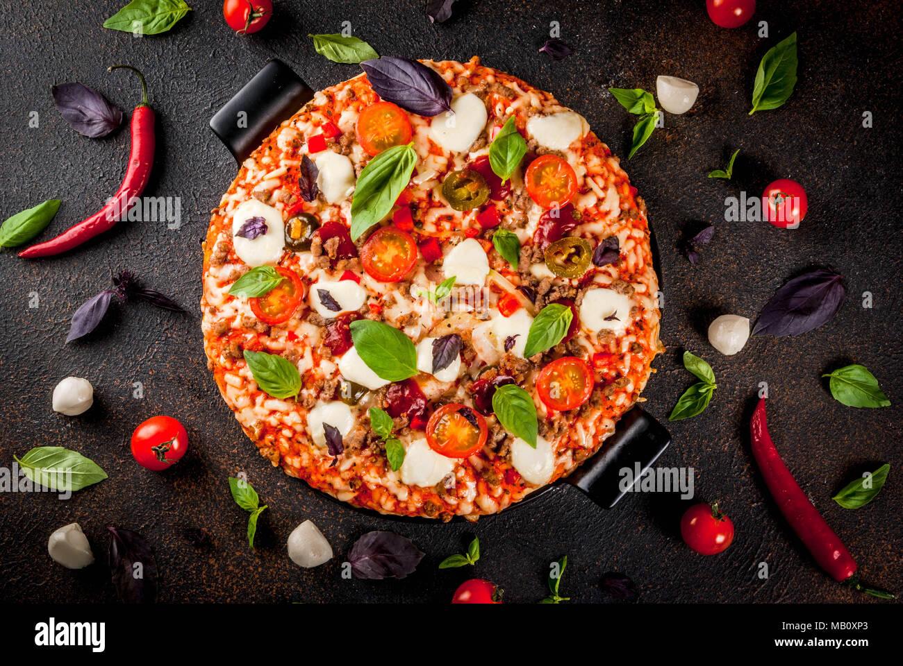 Pizza italienne sur la grille de sélection avec divers ingrédients sur fond sombre (top view copy space Photo Stock
