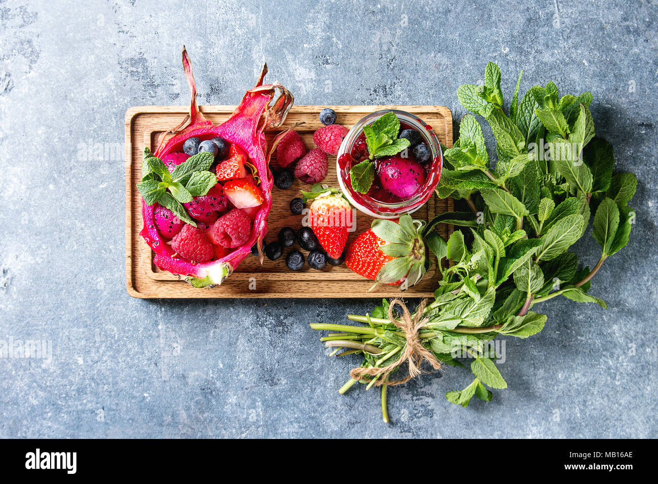 Vegan salade de fruits avec les petits fruits et de menthe servi en rose fruit du dragon avec les ingrédients ci-dessus sur sol en bois servant au blue texture background. Top v Banque D'Images