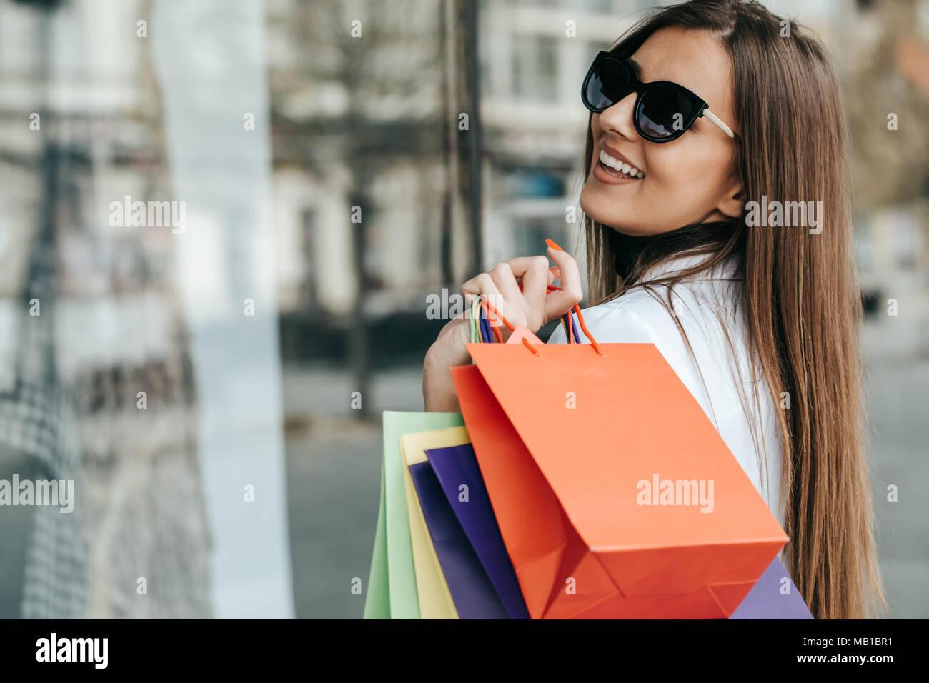 Belle jeune femme à l extérieur avec beaucoup de sacs. Portrait de jeune  femme accro dans les vêtements à la mode avec surprise face. 0708cad0e383