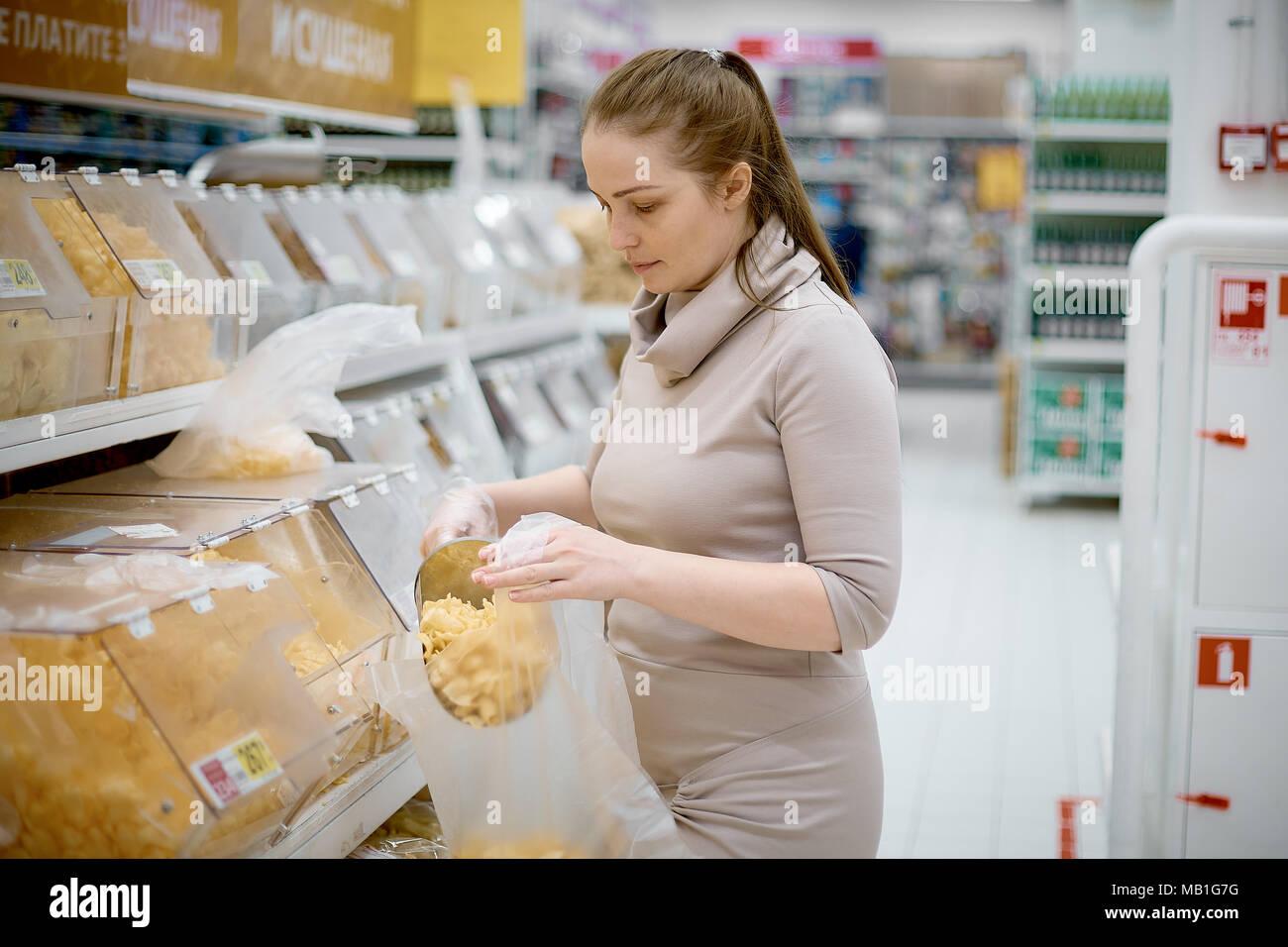 Belle jeune femme achète jetons sur poids dans les supermarchés Photo Stock