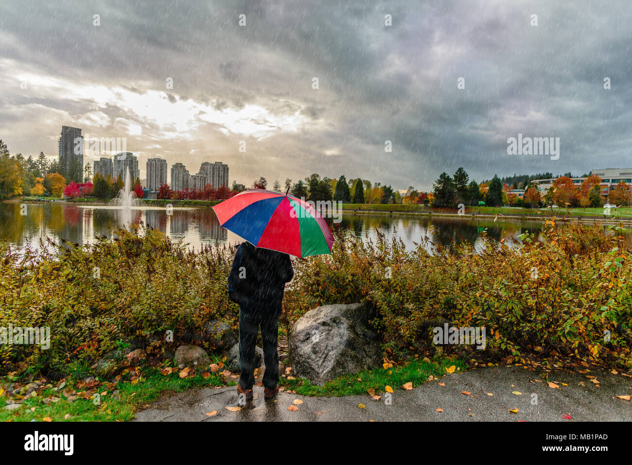 Hauteur Ciel De Pluie un homme avec un parapluie se tient sous la pluie dans un