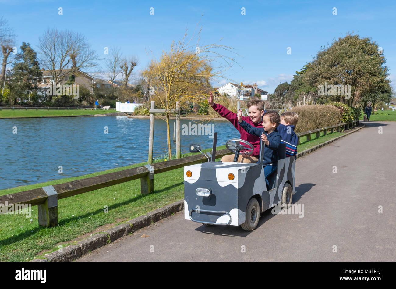 Les jeunes passagers de monter sur un véhicule motorisé de l'enfant dans un parc, tout en agitant à personnes, au Royaume-Uni. Photo Stock