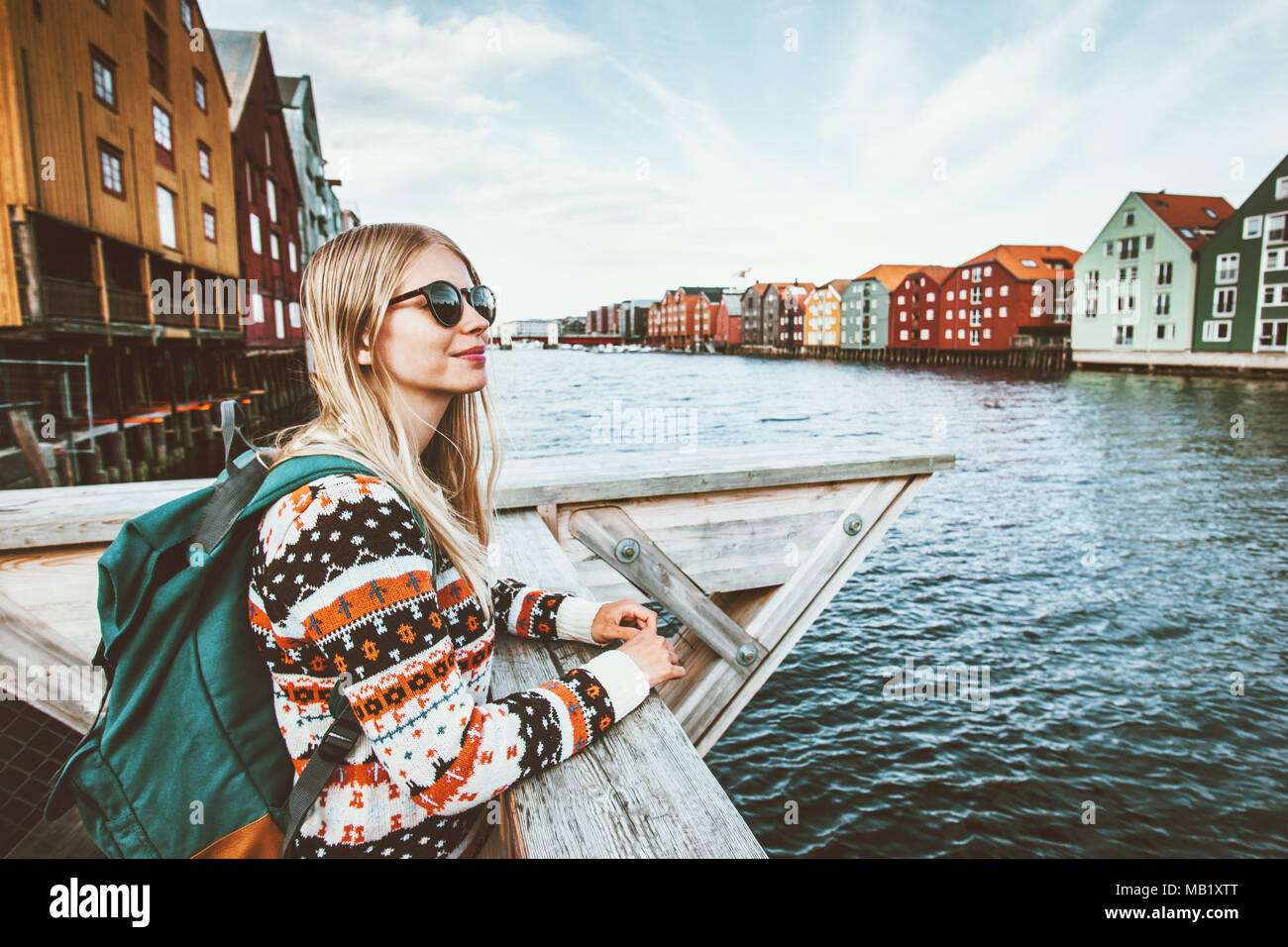 6fcddea7ac Jeune blonde femme voyageant dans la ville de Trondheim en Norvège vacances  week-end en plein air avec touristiques vie fille sac à dos visites  architecture ...