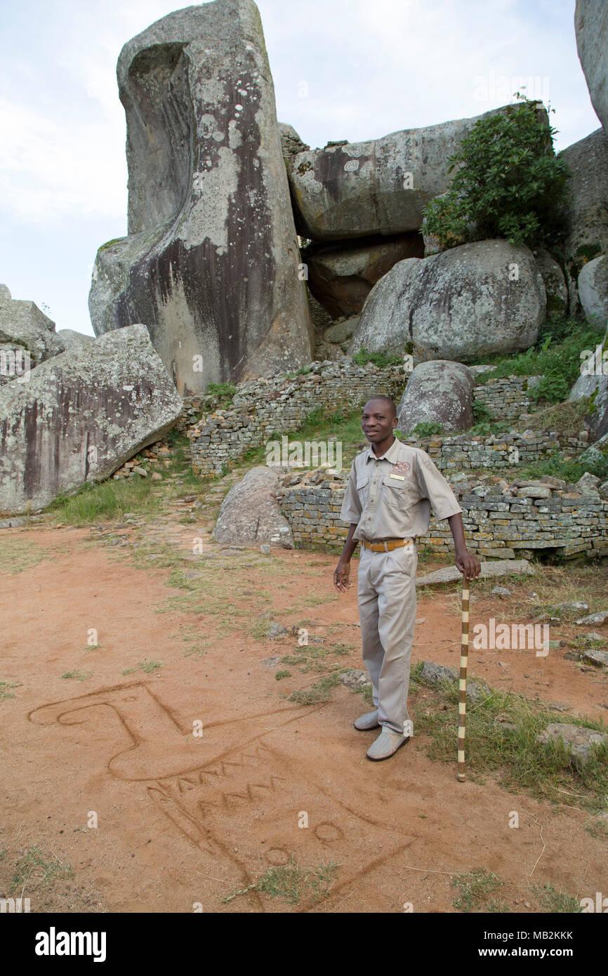 Lovemore, un guide, il esquisse la forme de l'oiseau sur le Zimbabwe Le Zimbabwe près de Masvingo au Zimbabwe. Photo Stock