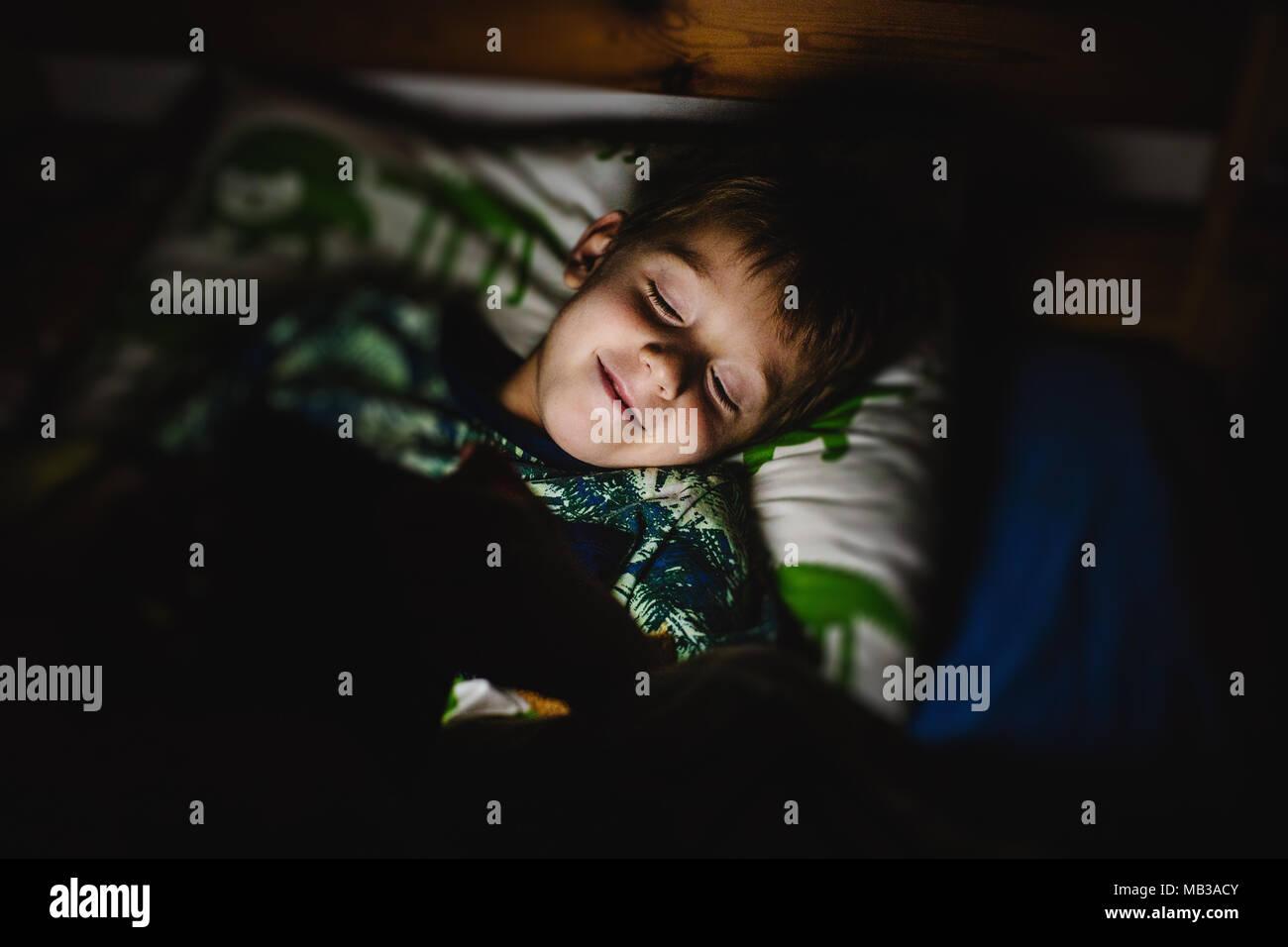 Jeune garçon lisant un livre électronique avec lumière intégrée au lit avant de dormir. La technologie dans la vie quotidienne des enfants. Fond sombre, basse lumière. Photo Stock