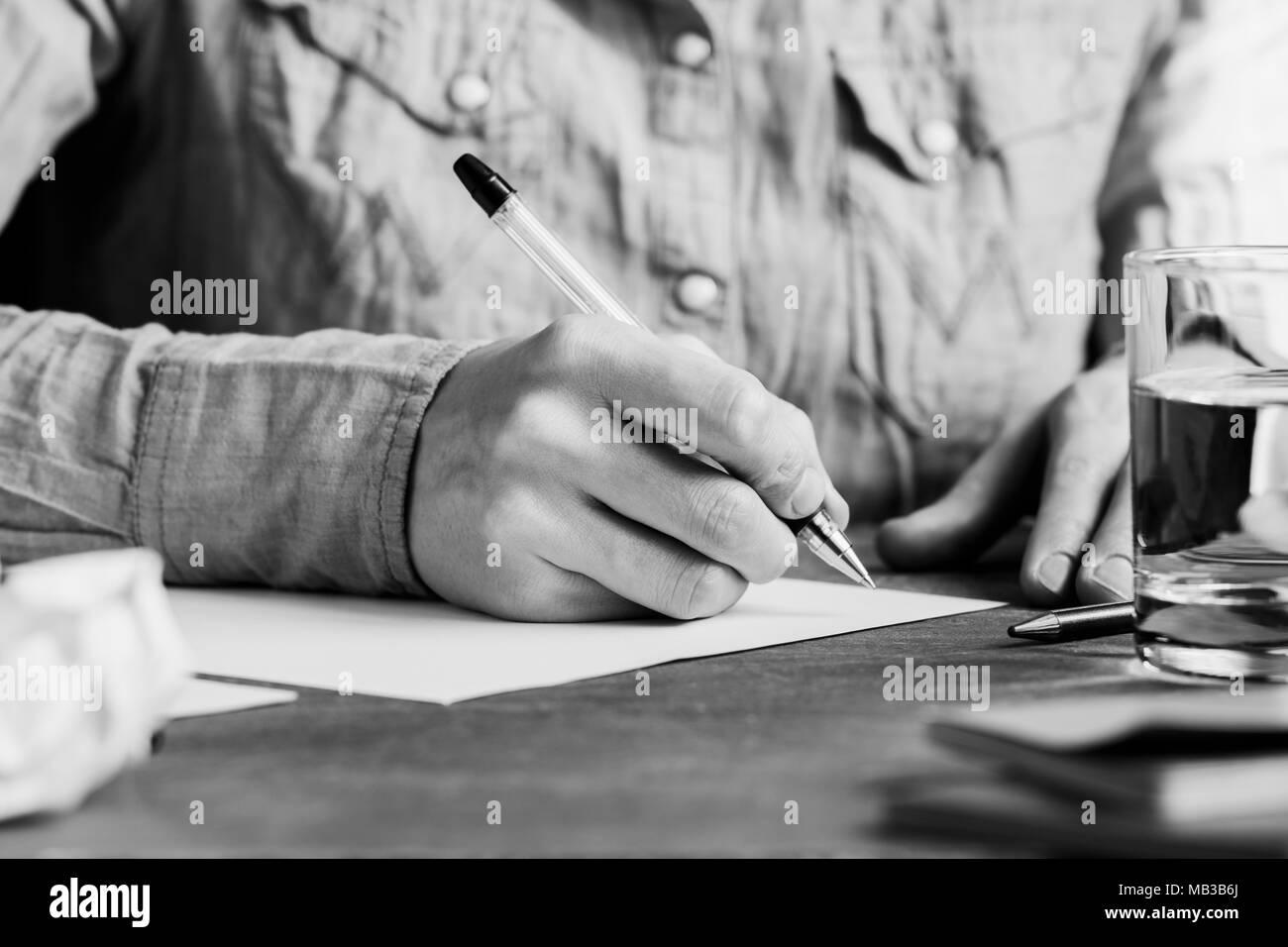 L'homme est écrit sur une feuille de papier blanc dans un milieu de travail. Le concept d'une œuvre et de l'éducation. La photographie en noir et blanc. Banque D'Images