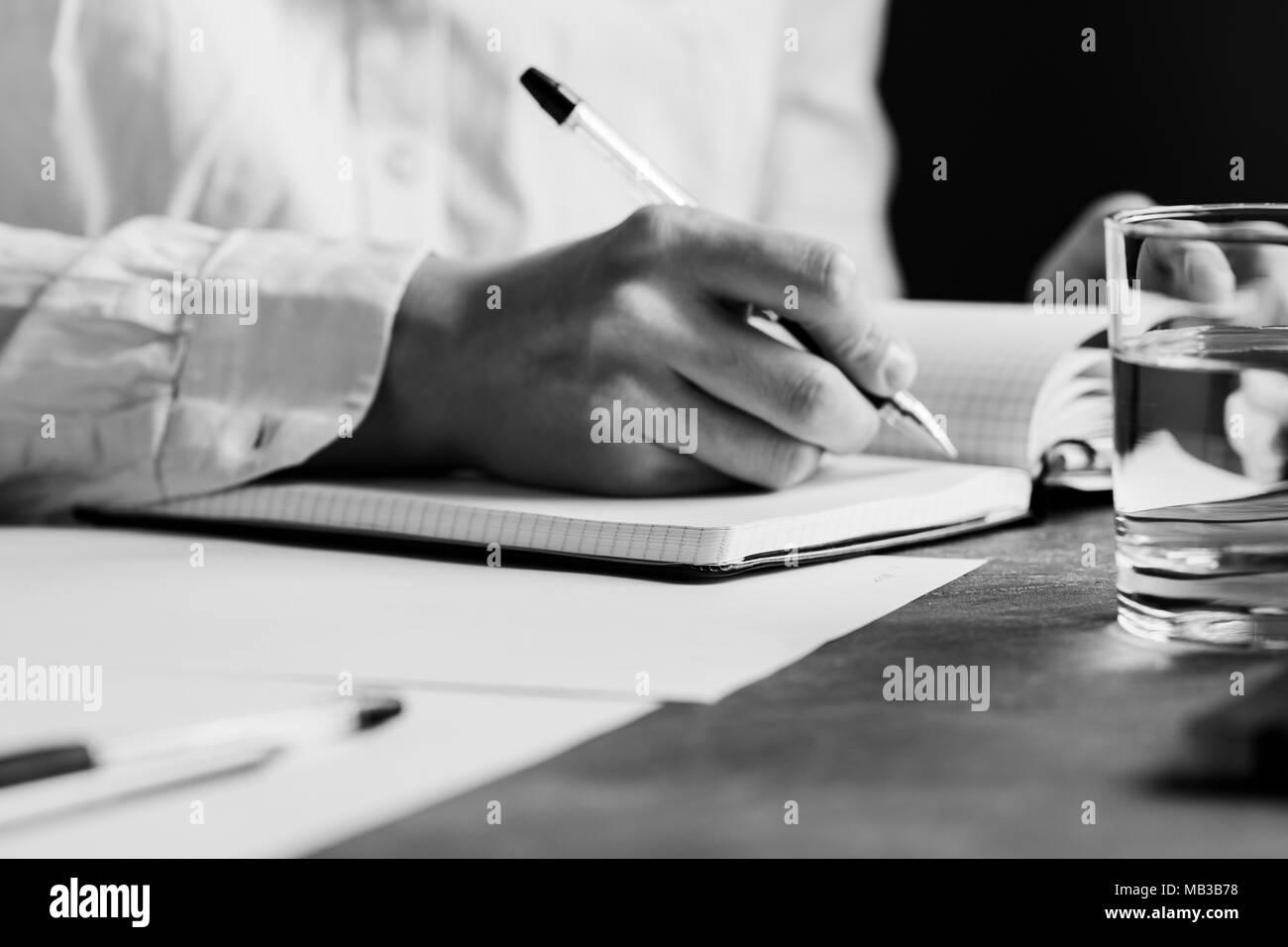 L'homme est écrit dans un ordinateur portable dans un lieu de travail. Le concept d'une œuvre et de l'éducation. La photographie en noir et blanc. Banque D'Images