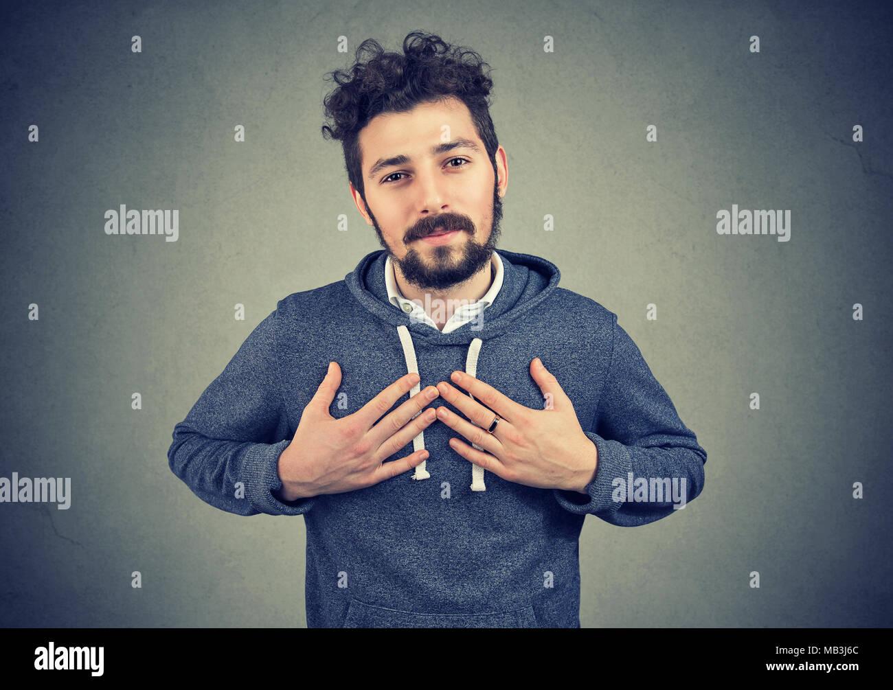 Homme fidèle garde les mains sur la poitrine près de cœur, montre la bonté exprime des émotions sincères, être gentil et honnête. Photo Stock