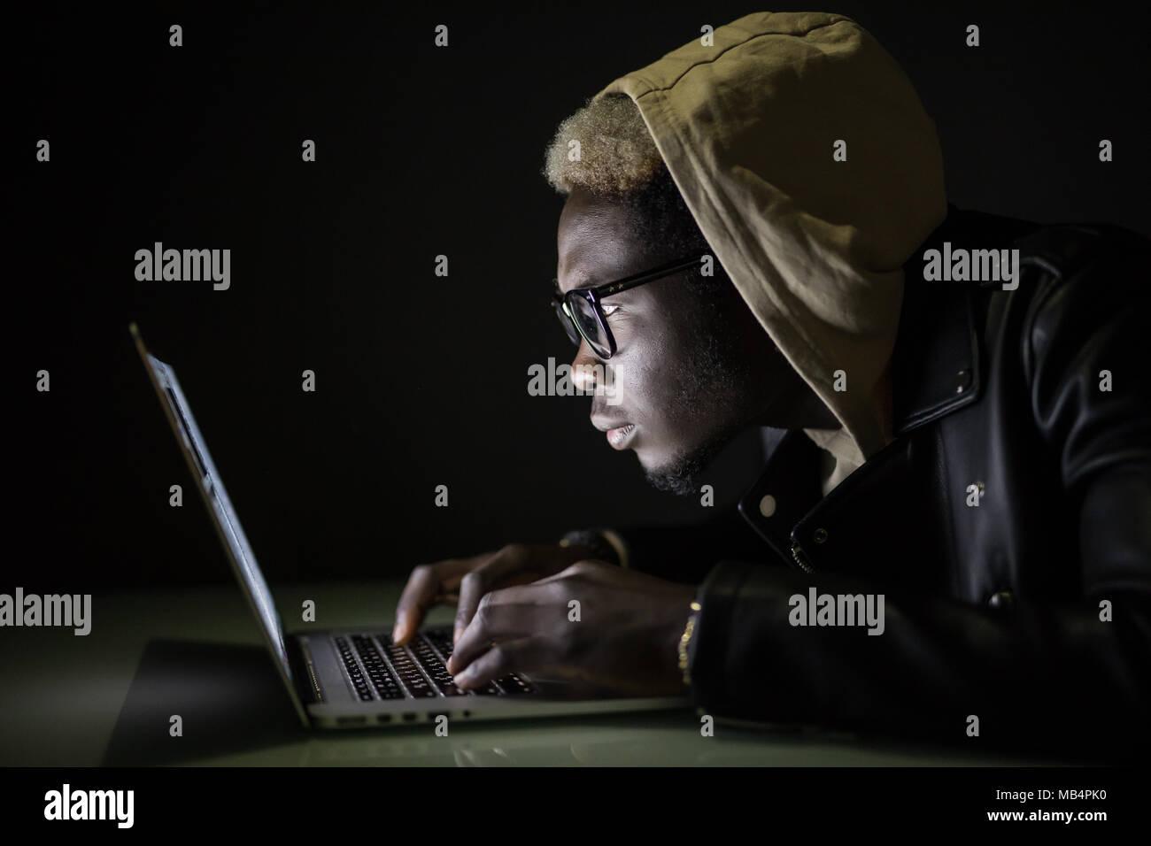 Homme beau à l'aide d'un ordinateur portable jusqu'à tard dans internet explorer Photo Stock