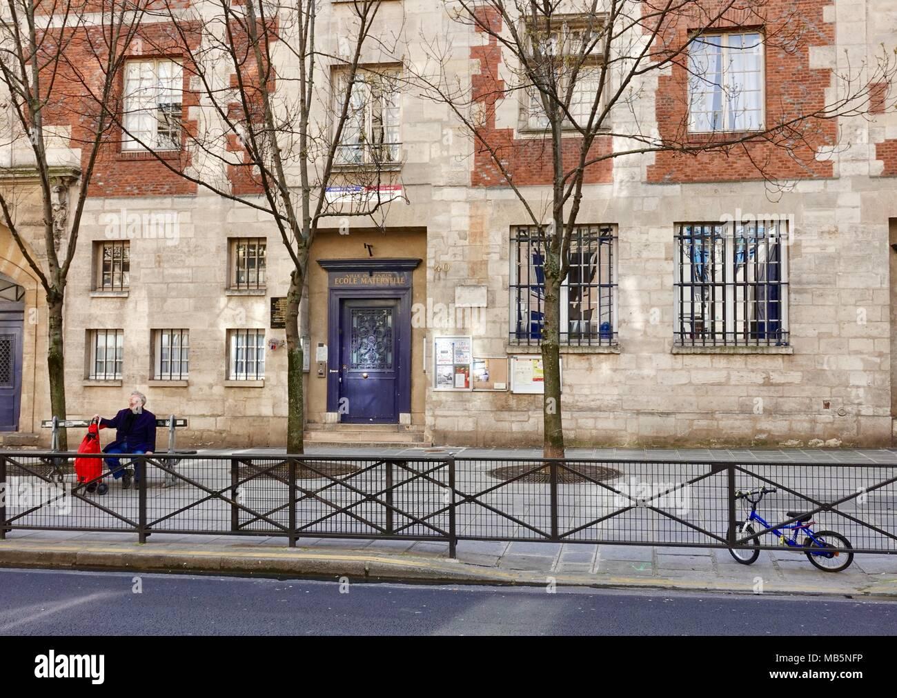 Homme avec un panier rouge est assis sur un banc en face de l'école maternelle, l'école maternelle française, 4e arrondissement, Paris, France Banque D'Images