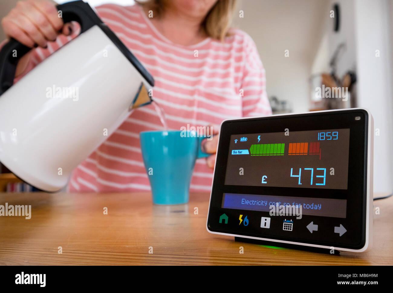 Moniteur d'énergie ( compteur intelligent )dans la cuisine d'une maison comme une femme fait une tasse de thé Photo Stock