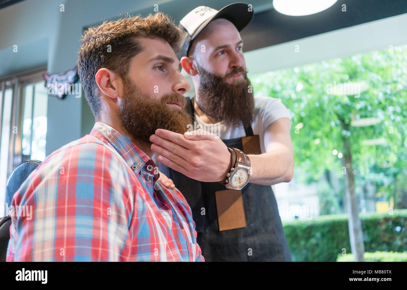 Jeune homme barbu pense à un changement de look dans le salon de coiffure Photo Stock