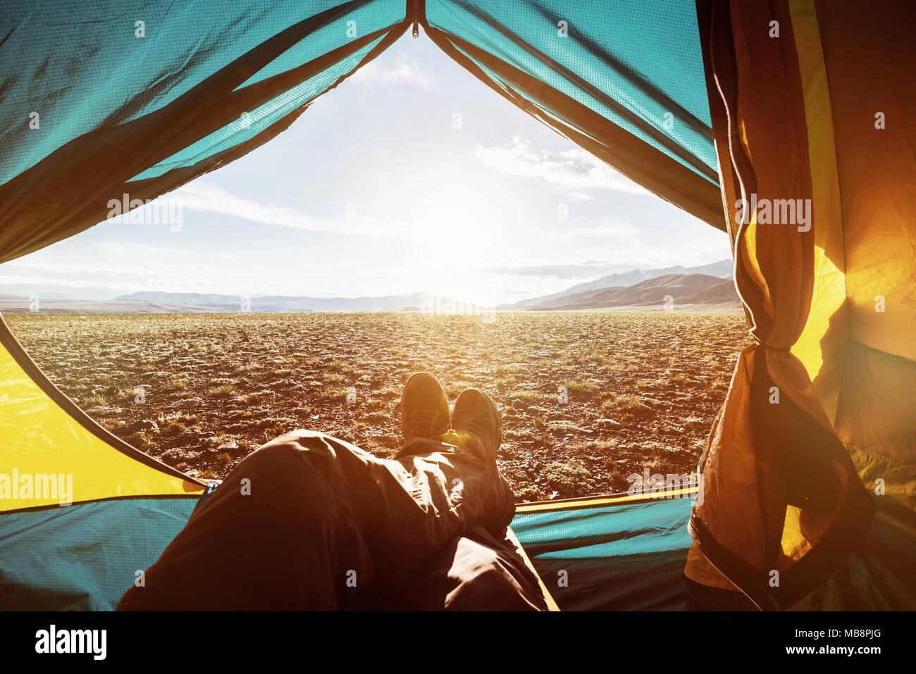 Les jambes de l'homme avoir touristique reste à l'intérieur de la tente Photo Stock