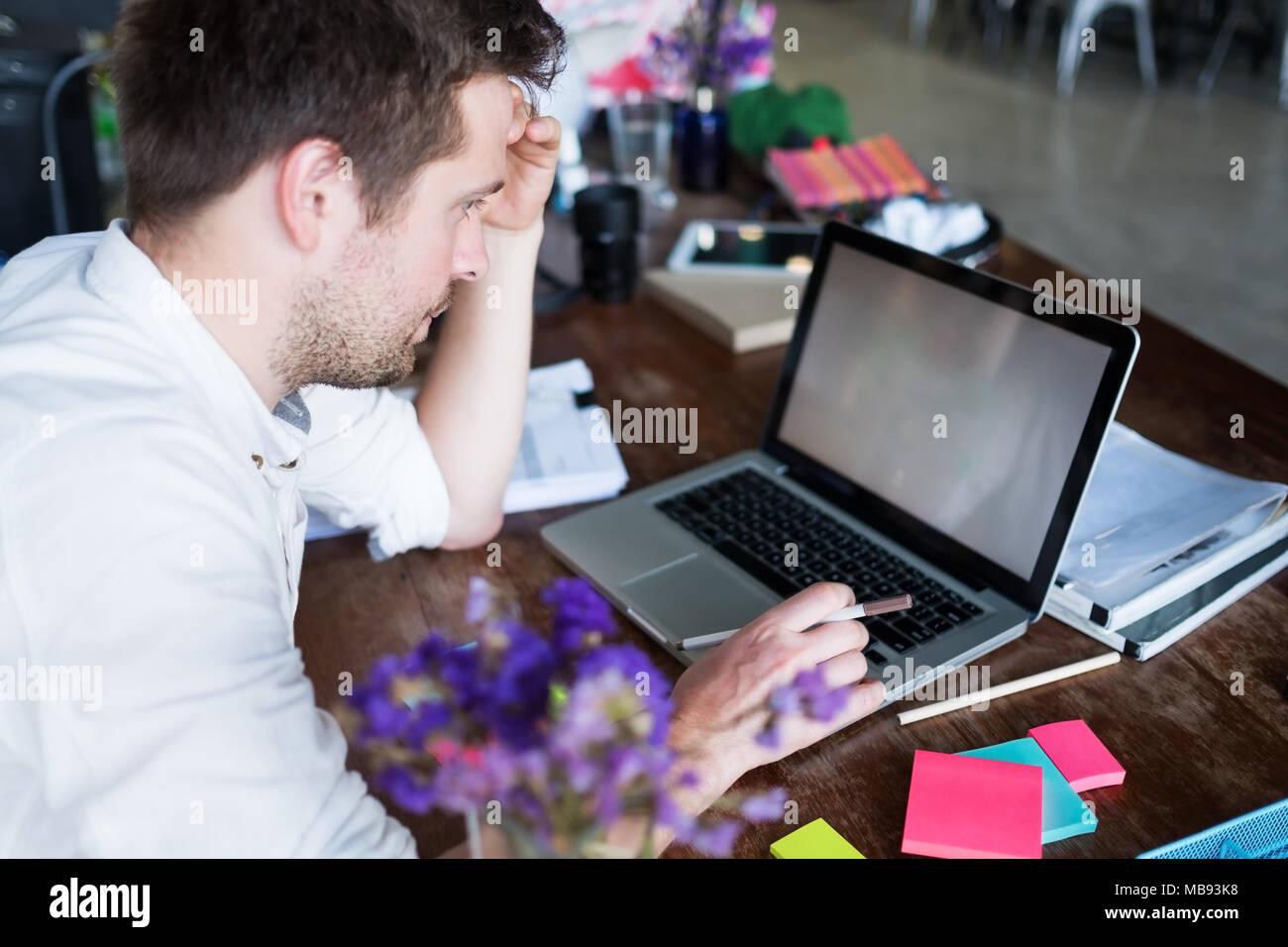 Caucasian man working on laptop assis à sa place de bureau moderne