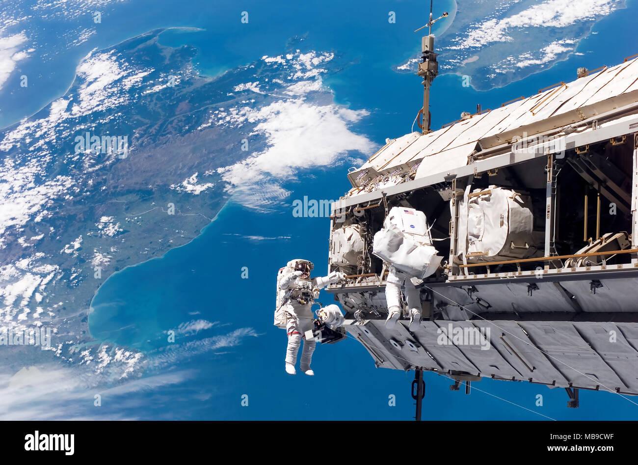 Les astronautes DE LA STATION SPATIALE INTERNATIONALE travaillant sur la construction de la poutre intégrée l'article le 12 décembre 2006. Les îles du nord et du sud de la Nouvelle-Zélande sont en dessous d'eux. Photo Stock
