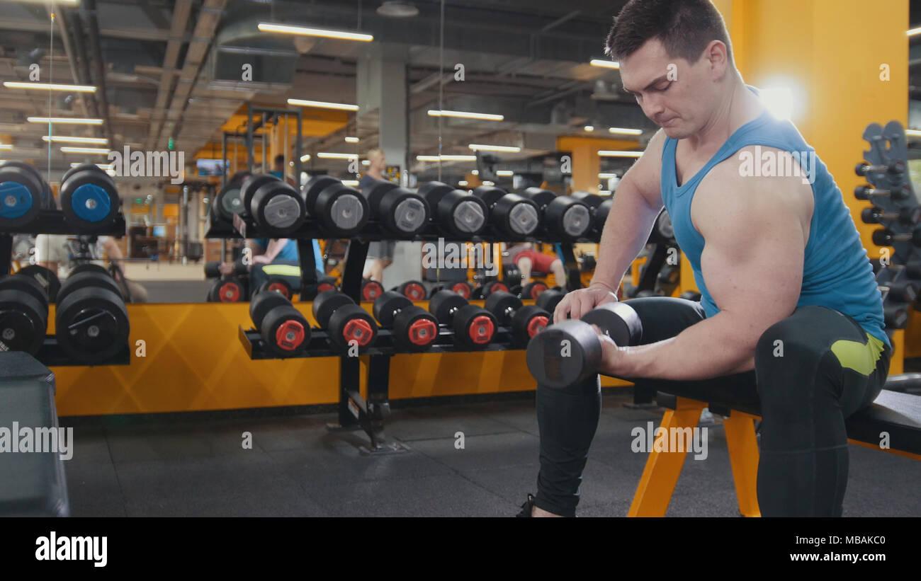 L'homme ne musculaire exercices d'haltères dans la salle de gym Photo Stock