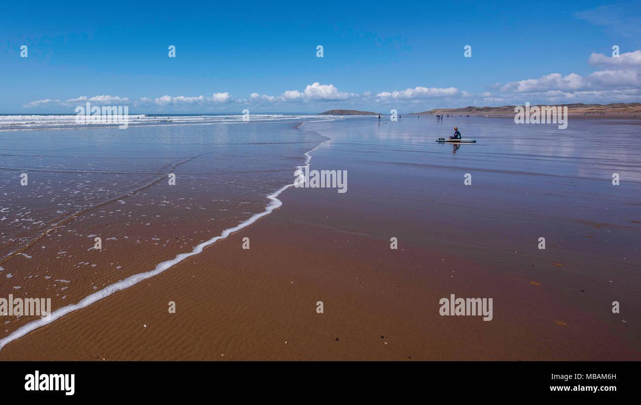 Un surfboarder reste sur la plage de Rhossili Bay, Gower, dans le sud du Pays de Galles, Royaume-Uni. Banque D'Images