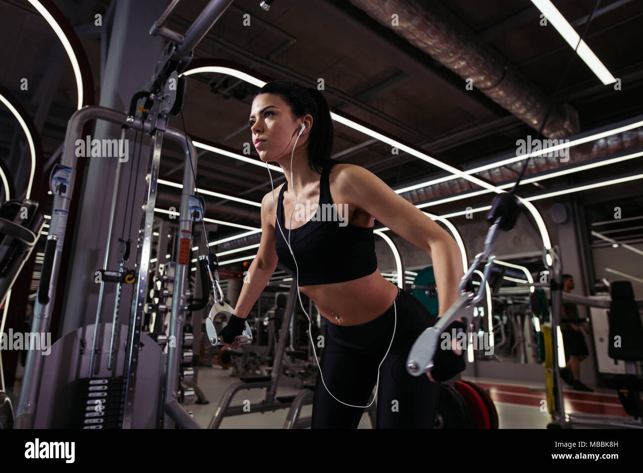 Fit woman exécuter l'exercice avec l'exercice-machine Cable Crossover in gym Photo Stock