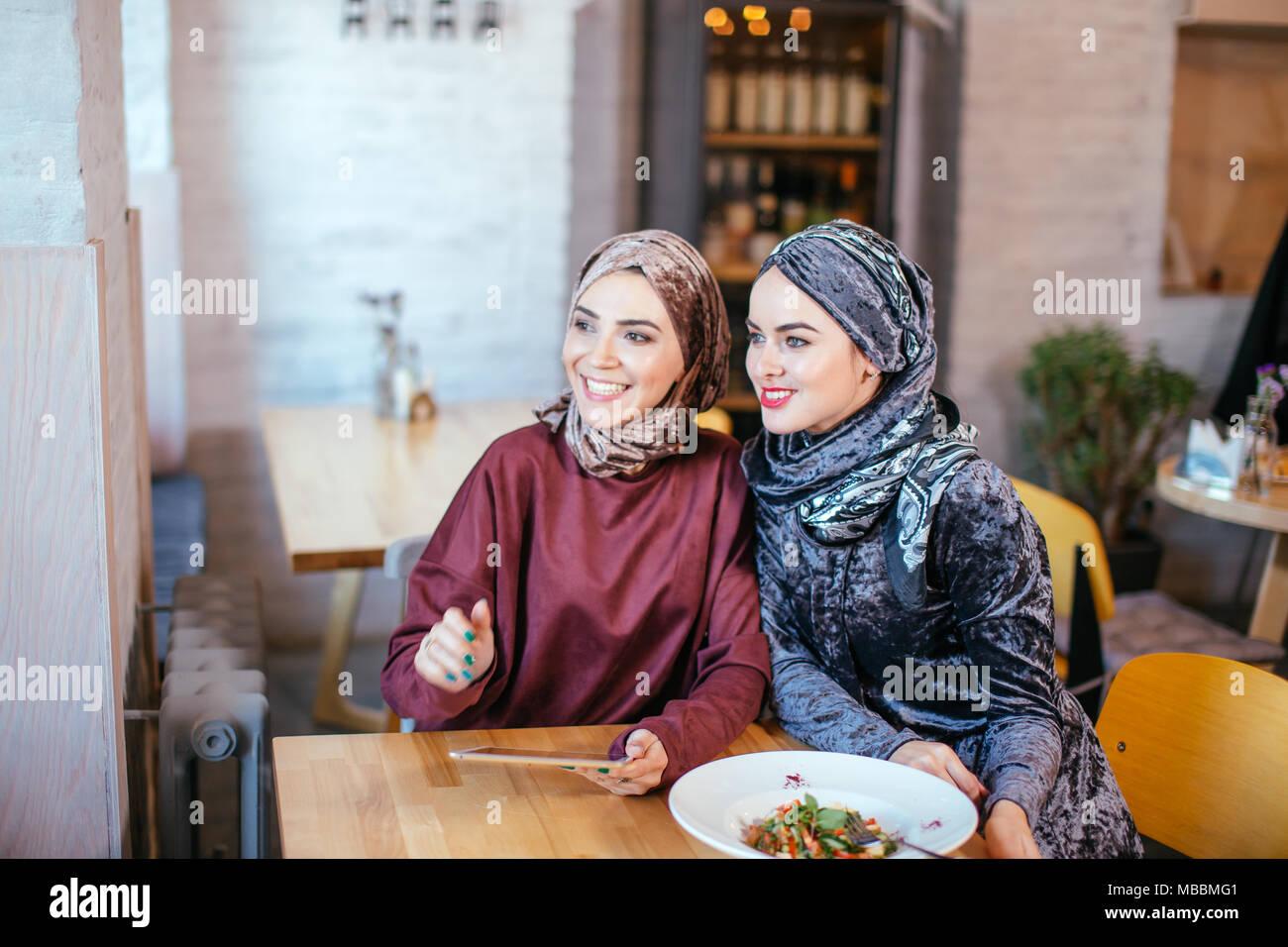 Deux femmes musulmanes au cafe, boutique en ligne à l'aide de tablette électronique Photo Stock