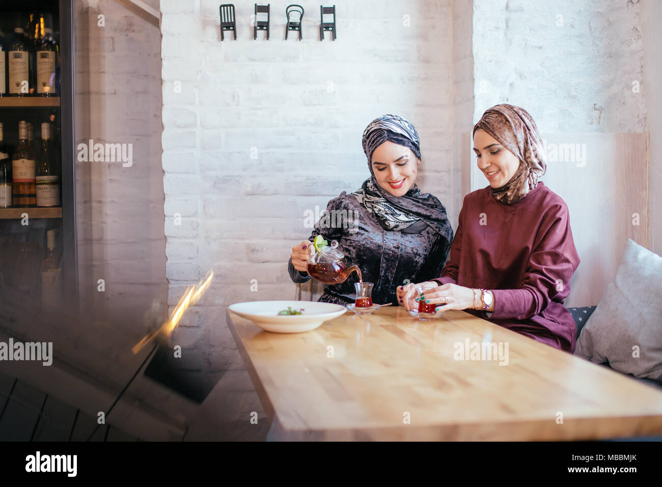 Deux musulmans caucasiens woman drinking tea in cafe Photo Stock
