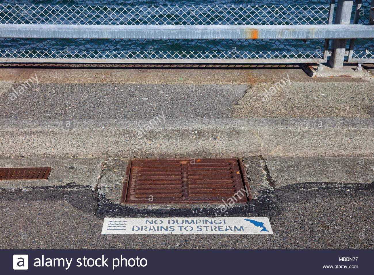 """Avec l'eau de Puget Sound dans l'arrière-plan, un signe à côté d'une vidange des eaux pluviales avertit les gens de ne pas déverser des produits toxiques. Le signe se lit """"pas de dumping Photo Stock"""